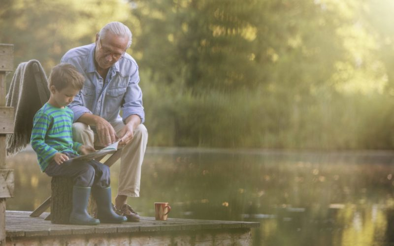 grandfather-and-grandson-reading-at-lake-555799527-5ac7c84143a1030036c1b221